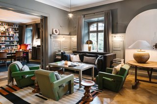 A Visual Journey Through Stockholm's Hotel Ett Hem - Photo 4 of 12 - The communal living room acts a social space where guests can mingle and relax. Cozy furniture and warm lighting makes the space feel more like a home than a hotel.