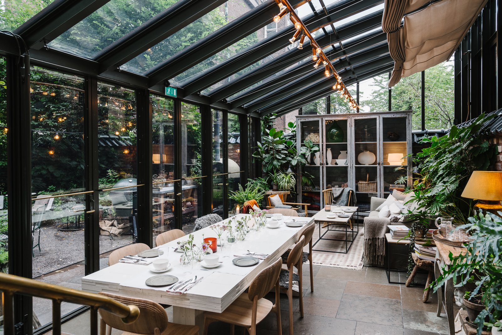 Crawford added a covered patio where guests can relax and enjoy a meal within the garden. The leafy glass house houses modern, natural-feeling wood furnishings and cozy textiles.