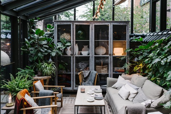 A Visual Journey Through Stockholm's Hotel Ett Hem - Photo 10 of 12 - Shown here is the lounge seating vignette in the covered patio/garden area, which is filled with greenery and furniture that's covered with warm textiles.