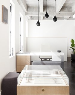Above Lee's custom desk hangs three matte black Drop Light Pendants that were designed by Early Work.