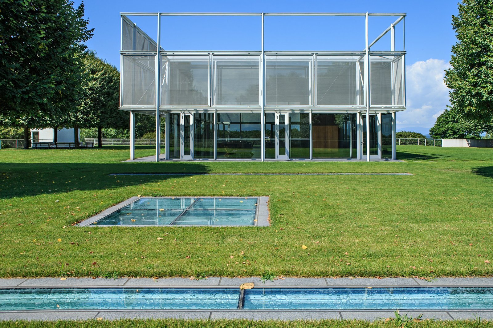 The house includes 7,000 square feet of substructure that sits on the underside of the hill from one side, and is open to the sky on the other. The glass plates seen at the forefront of this image serve as skylights to the substructure, which includes an indoor pool, mudroom, library, kitchen, gym, media room, and a walk-in cheese locker and wine room. A Thomas Phifer-Designed Glass-and-Steel Masterpiece For Sale - Photo 4 of 15