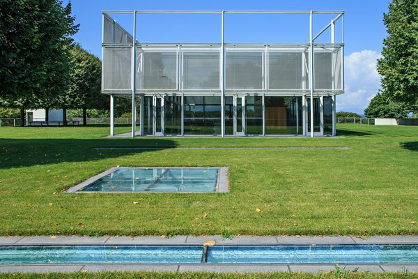 The house includes 7,000 square feet of substructure that sits on the underside of the hill from one side, and is open to the sky on the other. The glass plates seen at the forefront of this image serve as skylights to the substructure, which includes an indoor pool, mudroom, library, kitchen, gym, media room, and a walk-in cheese locker and wine room.