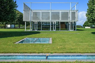A Thomas Phifer-Designed Glass-and-Steel Masterpiece For Sale - Photo 3 of 14 - The house includes 7,000 square feet of substructure that sits on the underside of the hill from one side, and is open to the sky on the other. The glass plates seen at the forefront of this image serve as skylights to the substructure, which includes an indoor pool, mudroom, library, kitchen, gym, media room, and a walk-in cheese locker and wine room.