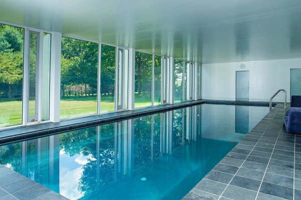 The substructure features an indoor pool, which looks out through glass walls on the side that's exposed to the ground level.
