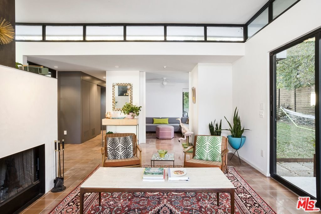 The open layout is connected to private gardens with floor-to-ceiling glass.