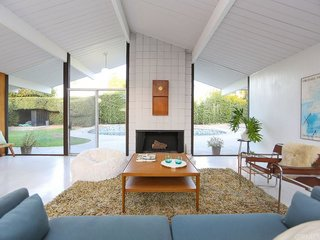 This Quintessential Eichler Will Hit All Your Midcentury Goals—and It's For Sale - Photo 2 of 7 - The living space—which looks past a fireplace and out to the pool—sits under original beamed ceilings with a characteristic A-frame shape.