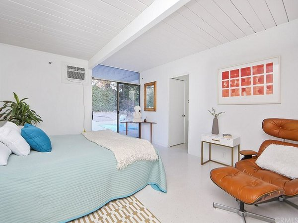 The house includes four bedrooms and two bathrooms, which have been updated. This bedroom exits directly onto the backyard patio.