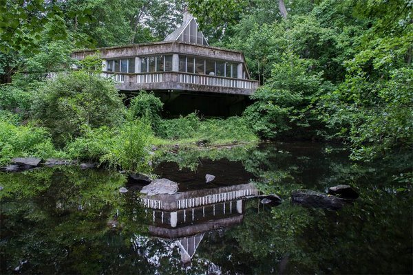 Though the house is in need of some dire repairs—including leaks and a lack of heat and water—it stands proud with its original architecture built entirely of concrete and glass. It cantilevers over the Silvermine River.  Photo 1 of 11 in The One-of-a-Kind Home of the Late Architect John Black Lee Drops to $750K