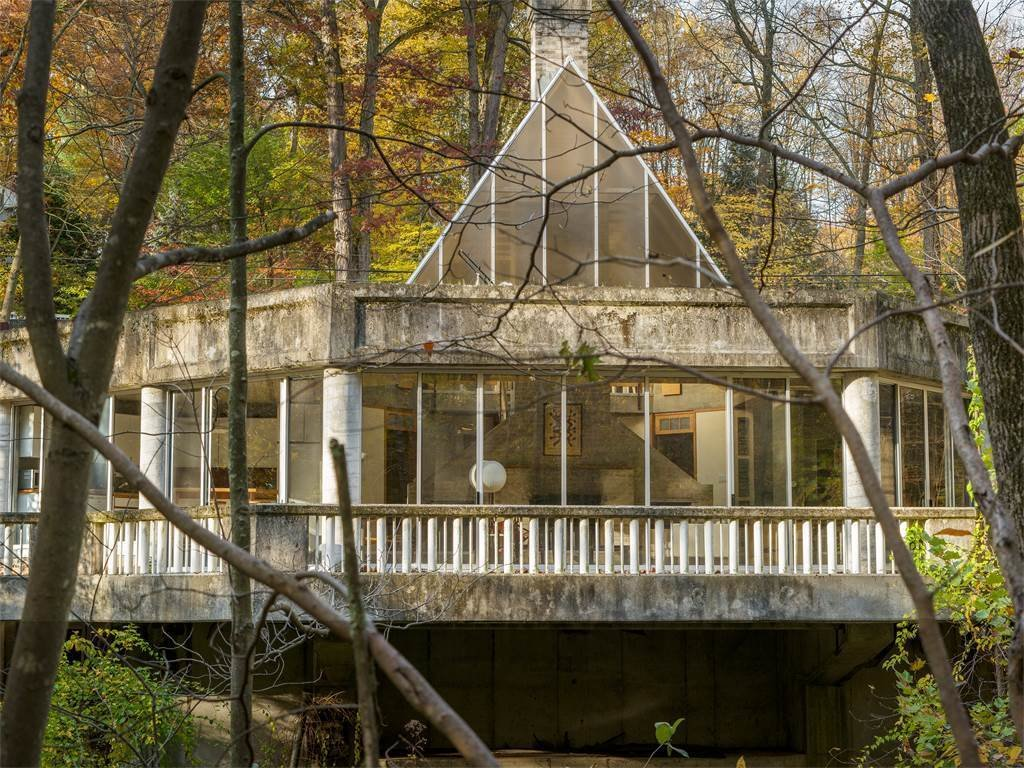 Though the house is in need of some dire repairs—including leaks and a lack of heat and water—it stands proud with its original architecture built entirely of concrete and glass. It cantilevers over the Silvermine River.  Photo 3 of 11 in The One-of-a-Kind Home of the Late Architect John Black Lee Drops to $750K