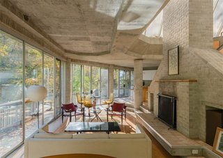 The One-of-a-Kind Home of the Late Architect John Black Lee Drops to $750K - Photo 5 of 10 - The living spaces and dining room are connected and feature an original fireplace. The concrete foundation is exposed throughout, accentuating the house's angular lines.
