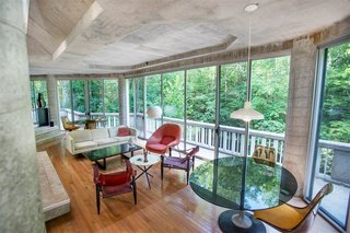 The One-of-a-Kind Home of the Late Architect John Black Lee Drops to $750K - Photo 7 of 10 - The interior hosts an open floor plan and looks out over a balcony that runs the length of the structure along the river side.