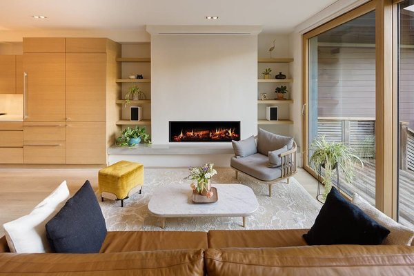 A Toronto-Based Firm Breathes New Life Into a Victorian's Interior - Photo 2 of 3 - Thanks to a hidden screen that rolls down over the fireplace, the living room doubles as a TV or movie room.