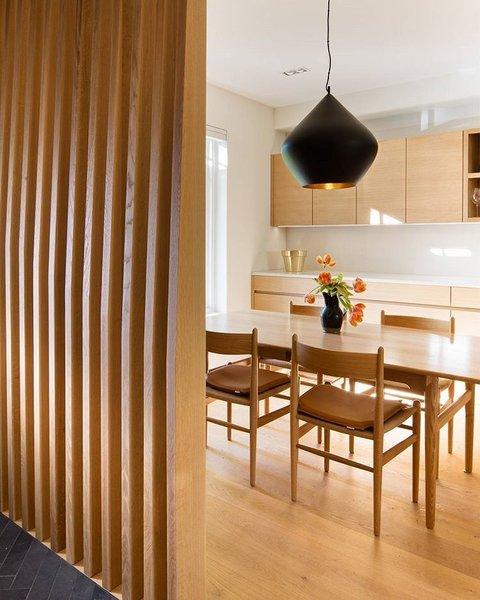 A Toronto-Based Firm Breathes New Life Into a Victorian's Interior - Photo 1 of 3 - The dining area is separated from the entrance with a custom wrap-around screen that provides privacy without closing the space off completely. The slats are made of CNC'ed wood.