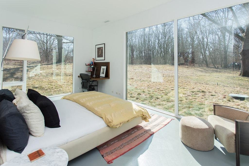 The bedrooms look out to the wooded surroundings through large expanses of glass.