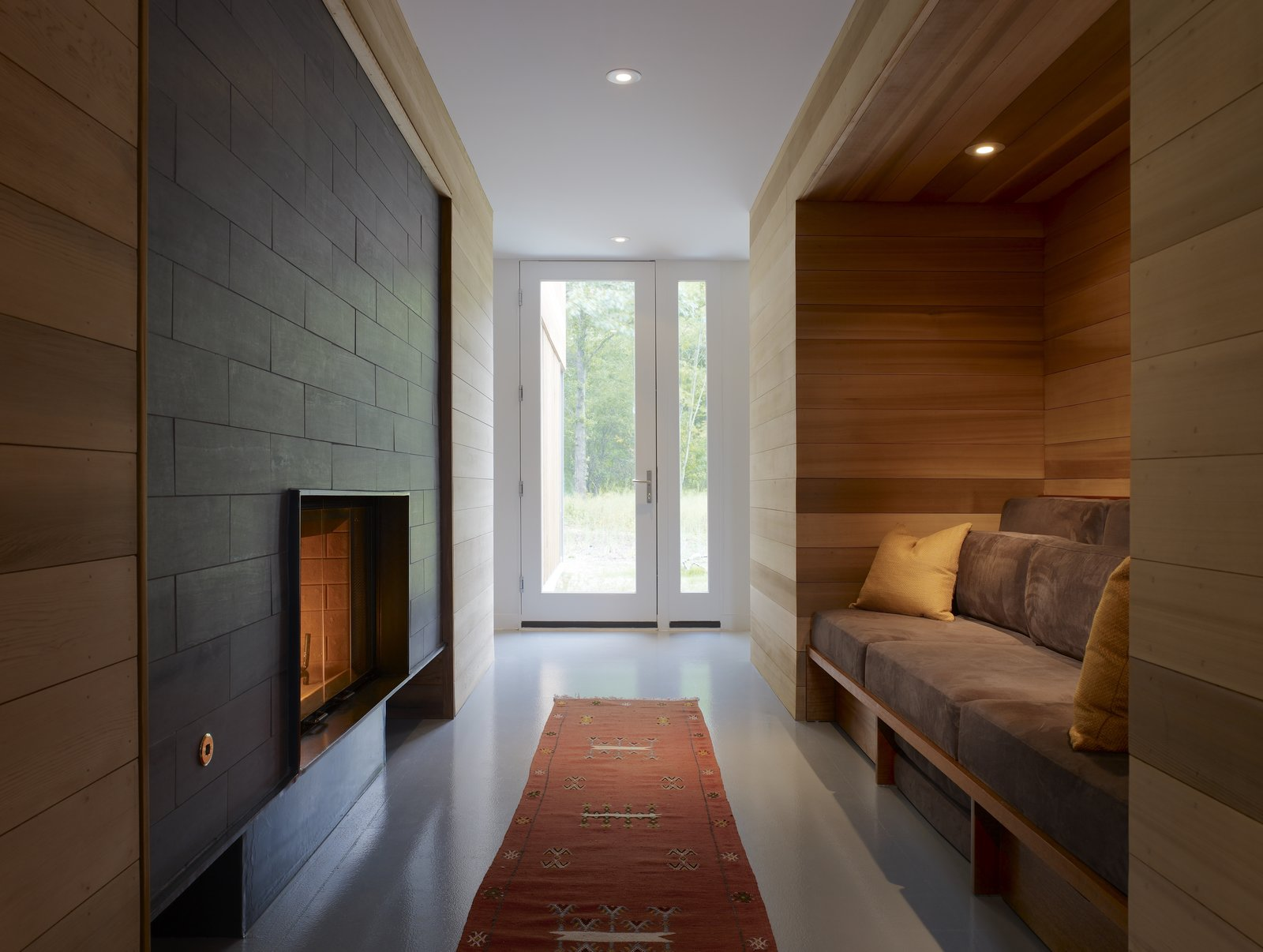 Entering through the front door leads you to an inglenook, where Lynch installed a fireplace and a custom built-in seating area that's surrounded by red cedar.