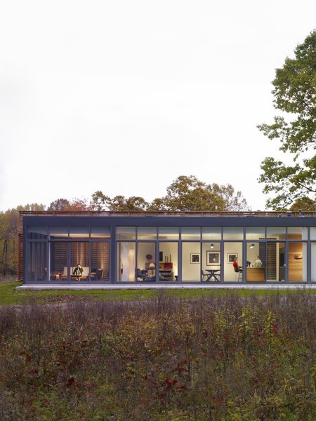 The glass-enclosed side of the house reveals a screened porch on the left, followed by a combined open area that brings together the living space, dining area, and the kitchen.