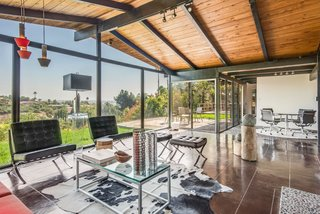 This Midcentury Home For Sale Is Not Your Regular Ranch House - Photo 3 of 9 - When you enter into the house, you find yourself in an open space that combines the living and dining rooms—and is lined with floor-to-ceiling glass. The dining area is marked by the same aggregate concrete flooring that began in the front of the house.