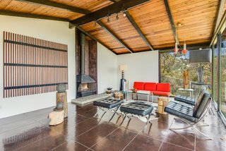 This Midcentury Home For Sale Is Not Your Regular Ranch House - Photo 5 of 9 - A wall of quarry tile surrounds the freestanding fireplace that takes centerstage in the living room. Cole pointed out that though it's original to the house, its initial orange color has been painted over.