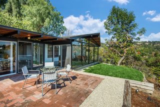This Midcentury Home For Sale Is Not Your Regular Ranch House - Photo 9 of 9 - The outdoor space can be accessed directly from the living area and includes a deck, lawn, and a section that's perfect for an outdoor dining table setup—which sits on top of terra cotta tile and more aggregate concrete floors.