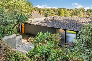 This Midcentury Home For Sale Is Not Your Regular Ranch House - Photo 1 of 9 - Nate Cole of Coldwell Banker explained that this home is possibly the only one of its kind in the neighborhood. The front of the house sits slightly hidden from the street and boasts a vibrant orange front door.