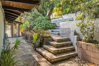 This Midcentury Home For Sale Is Not Your Regular Ranch House - Photo 2 of 9 - An impressive stone staircase leads down to the entrance of the house. Here, you'll also find an aggregate concrete floor treatment, which continues to be a theme throughout both the interior and exterior.