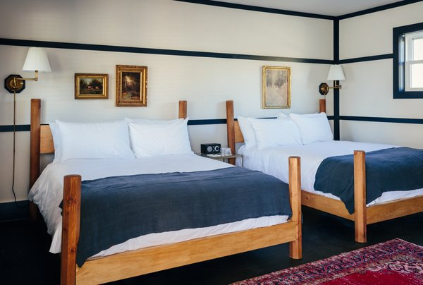 The twelve classic bedrooms are filled with raw brass light fixtures and beds that are custom designed by woodworker David E Cummings. Marked by octagonal posts, the frames are made out of solid pine and are handcrafted in his upstate studio.