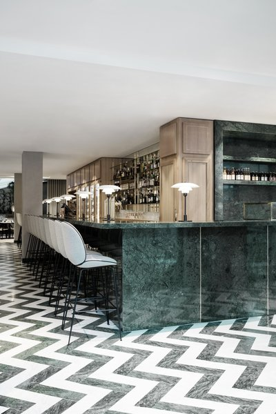 The entire space is filled with a green-focused color palette that's offset by shades of gray and brass details. The expansive green marble bar hosts GUBI's Beetle Bar Stools.