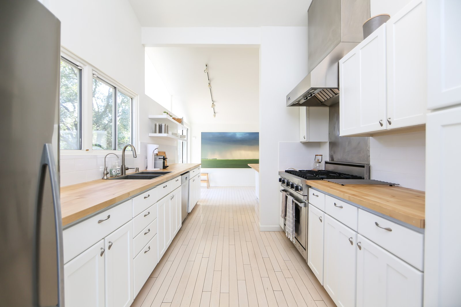 The original wood flooring remains in the kitchen and living rooms, while the kitchen was renovated with new surfaces and appliances.  Photo 5 of 10 in If You Crave Bright, Light-Filled Spaces, This Midcentury Home For Sale Could Be the One