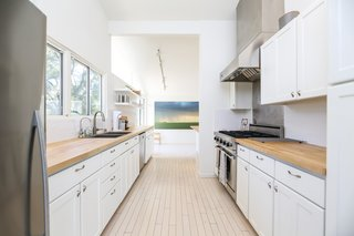 If You Crave Bright, Light-Filled Spaces, This Midcentury Home For Sale Could Be the One - Photo 4 of 9 - While the kitchen was updated with new surfaces and appliances, its original wood flooring has been kept intact.