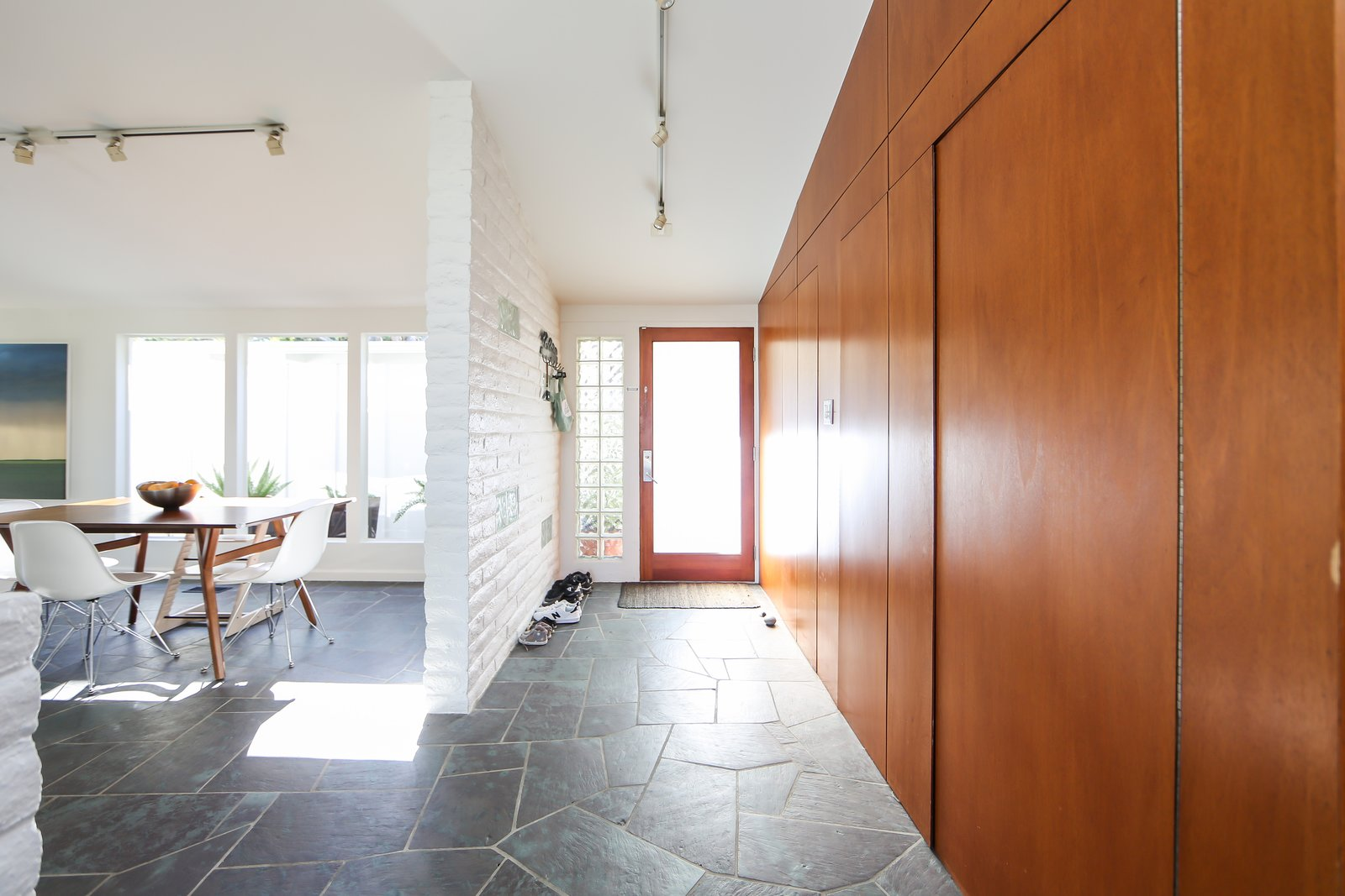 Similar to other Fickett homes—which the neighborhood is filled with—it includes original paneling throughout the home and brickwork that's been painted white.  Photo 6 of 10 in If You Crave Bright, Light-Filled Spaces, This Midcentury Home For Sale Could Be the One