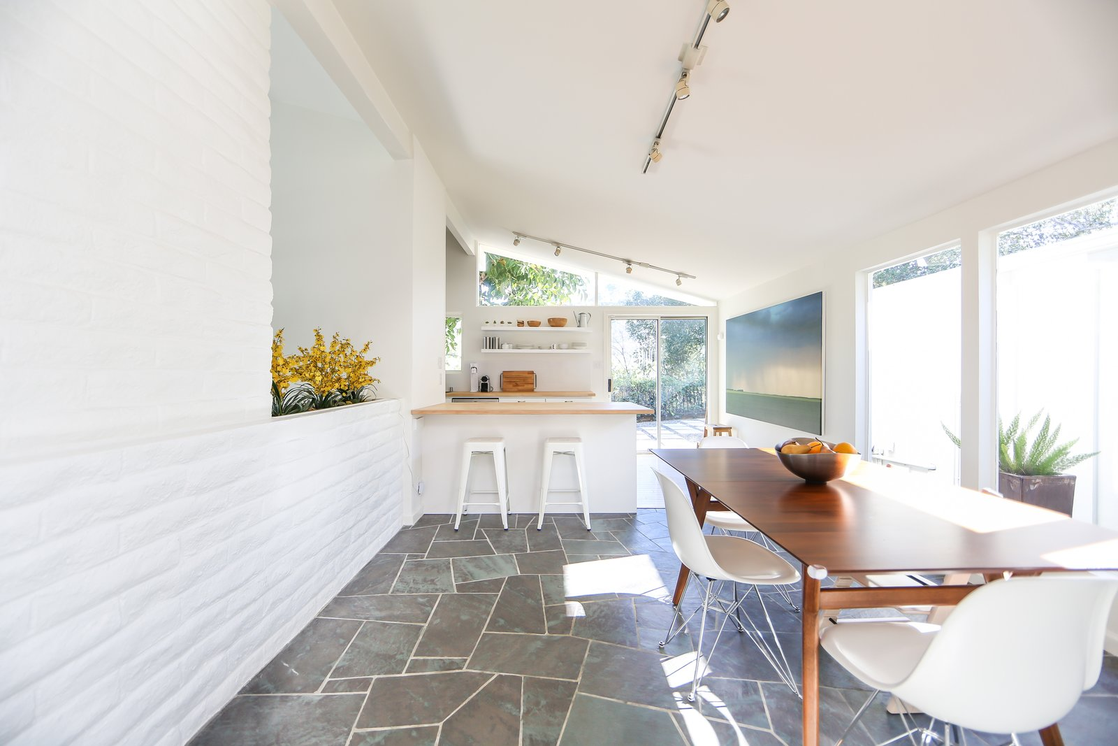 Though the main bones have been kept intact, one of the past owners installed slate flooring in the entryway, hallway, and dining area (shown here), which leads into the lengthy kitchen. If You Crave Bright, Light-Filled Spaces, This Midcentury Home For Sale Could Be the One - Photo 4 of 10