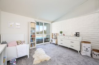 If You Crave Bright, Light-Filled Spaces, This Midcentury Home For Sale Could Be the One - Photo 8 of 9 - The bedroom that the current family turned into their daughter's room has one original brick wall and looks out to views of the pool.
