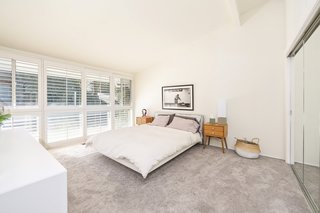 If You Crave Bright, Light-Filled Spaces, This Midcentury Home For Sale Could Be the One - Photo 7 of 9 - A past renovation included installing carpets into the bedrooms, which have been left clean and simple.