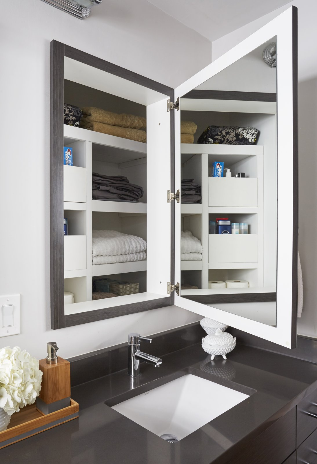 Though they made these changes to the vanity area, they preserved the depth behind the medicine cabinets for linen storage.  Photo 10 of 12 in Clever Storage Solutions and a Shifted Layout Revive This 1950s Chicago Home