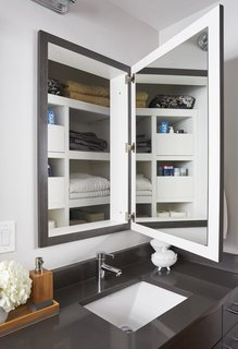 Clever Storage Solutions and a Shifted Layout Revive This 1950s Chicago Home - Photo 10 of 12 - Though they made these changes to the vanity area, they preserved the depth behind the medicine cabinets for linen storage.