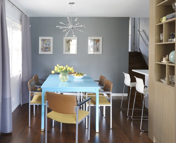 The dining room hosts a dining table that they found on Craig's List, which Carly painted this bright blue in the basement of her old apartment.