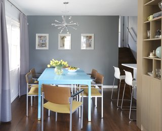 The dining room hosts a table that they found on Craig's List, which Carly painted bright blue in the basement of her old apartment.
