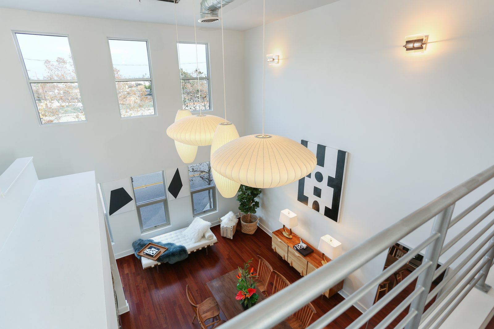 Shown here is the view of the living space from the lofted bedroom. The loft is being sold with the four-piece set of George Nelson bubble lamps that hang from the twenty-foot ceiling.