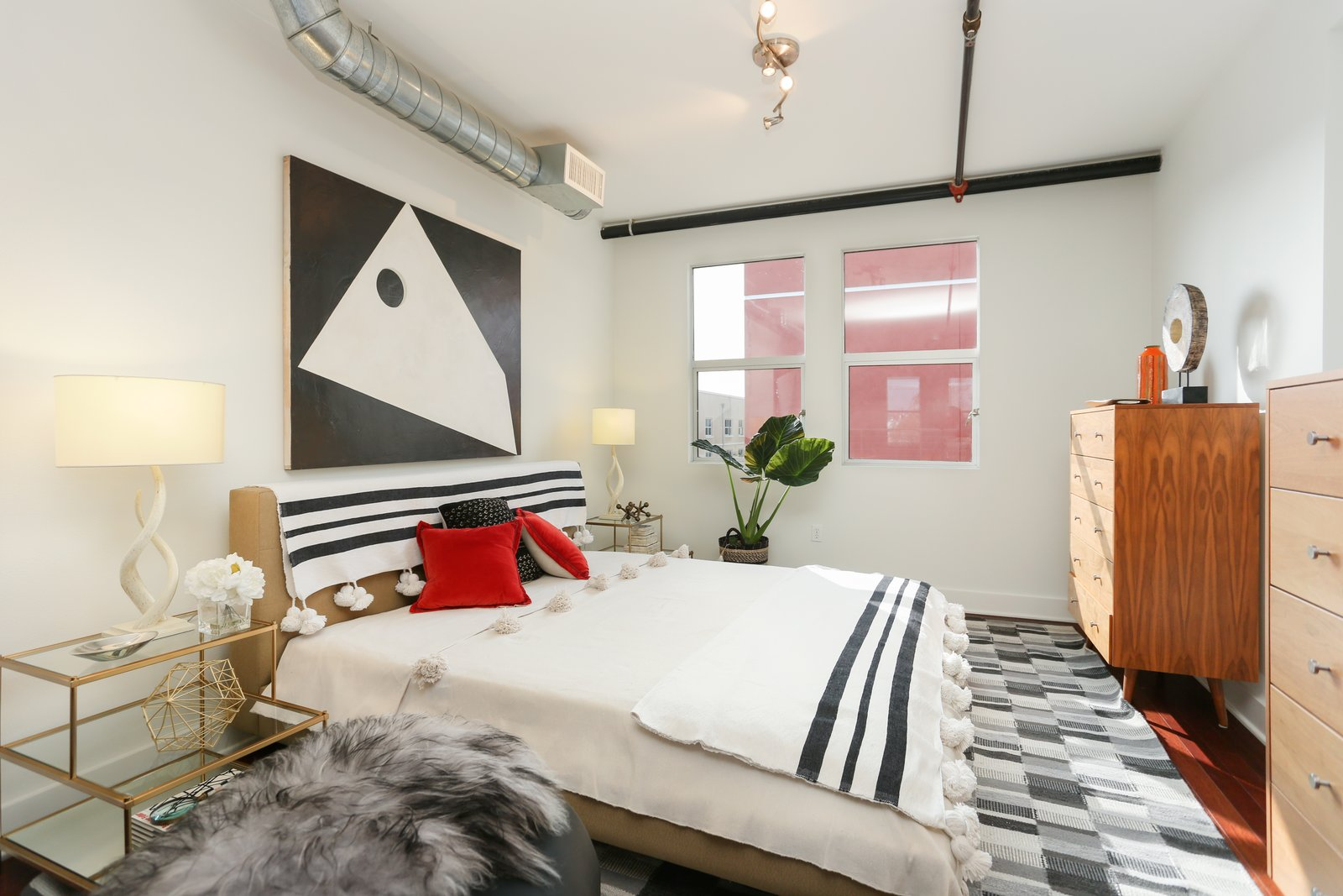 The bedroom is tucked into the loft space and sits under exposed air ducts and pipes—both of which add to the industrial vibe.  Photo 6 of 9 in A Designer Lists Her Three-Story Live/Work Loft in Orange County For $525K
