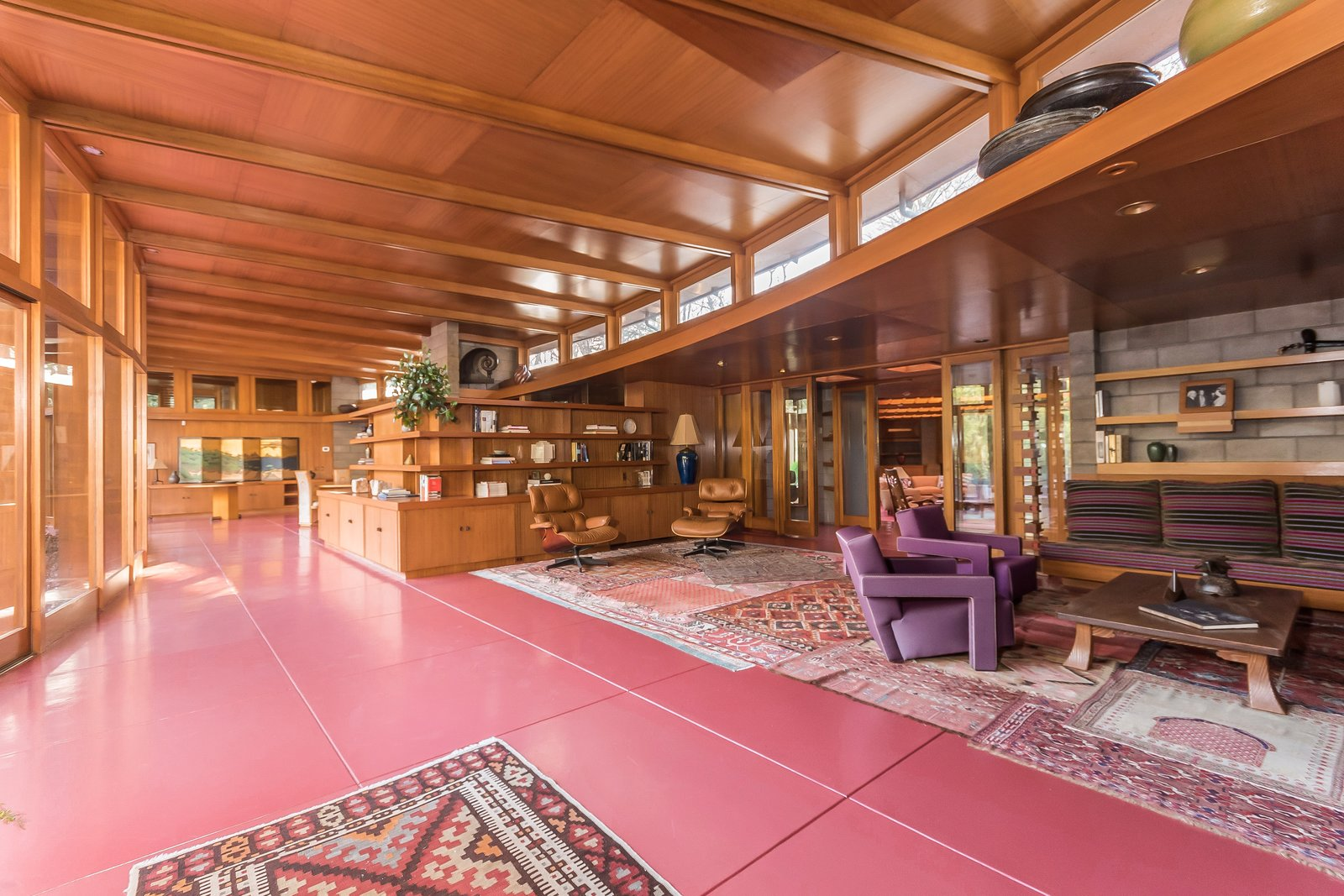 The red flooring that runs throughout the interior is Colorundum in Cherokee red, a color Wright loved to use in his projects. Jim Gricar of Houlihan Lawrence explains that it's a series of minerals that have a low freezing point, which makes it difficult to crack.