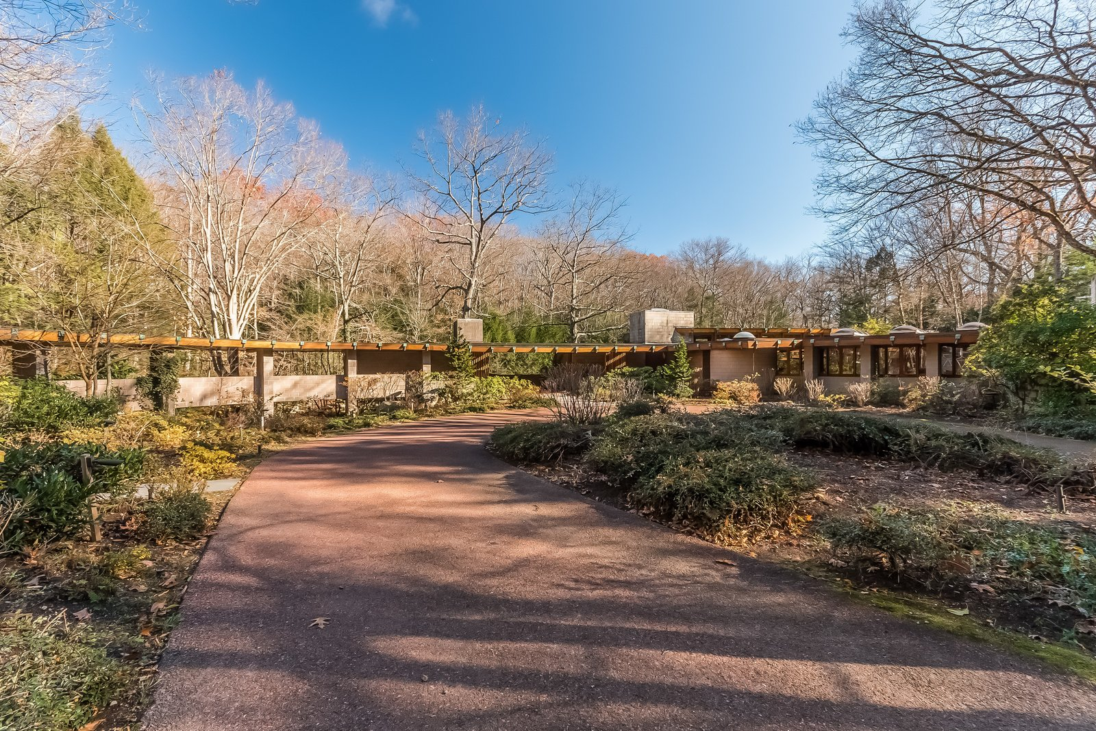 Shown from the front of the house, you can see that the structure is built in Frank Lloyd Wright's classic Hemicycle design. The main entrance to the house is under the chimney stack near the center, while the covered breezeway on the left leads to a four-car parking structure, the greenhouse, and the caretaker's quarters.  Photo 1 of 11 in Frank Lloyd Wright's Last Major Residential Masterpiece Could Be Yours for $7.2 Million
