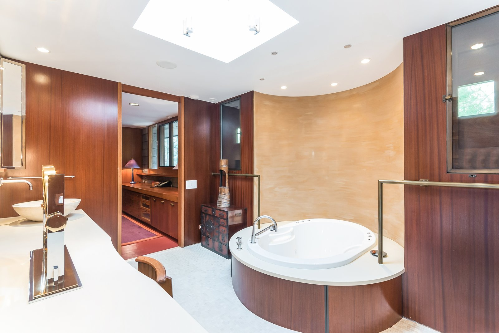 Shown here is one of the double master bathrooms, which holds a new tub that sits in front of a painted plaster wall. The layout and mahogany panels have remained original.  Photo 7 of 11 in Frank Lloyd Wright's Last Major Residential Masterpiece Could Be Yours for $7.2 Million