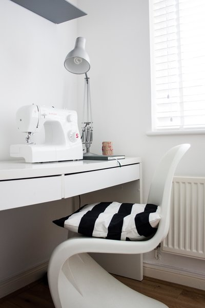 Silvia loves to sew and create in her spare time, which she does in her makeshift studio space, shown here with a desk from Ikea. Shown here is one of the cushions she made herself, which is done in the same fabric as the shower curtain in the bathroom.