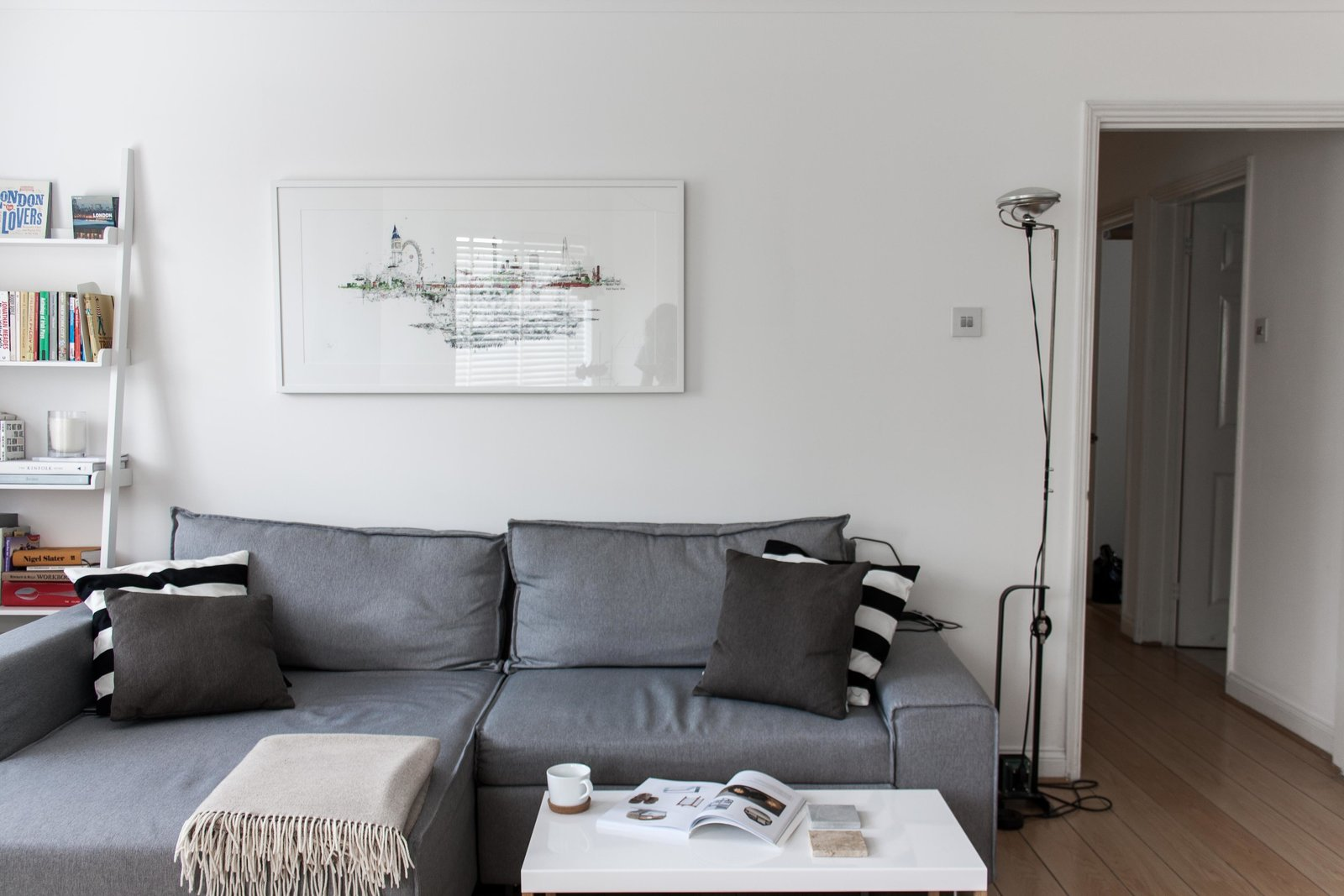 For the small yet open living space, Silvia included a sofa bed from Made.com, which can be easily pulled out for overnight guests. To the right of the sofa is the FLOS Toio Modern Floor Lamp by Achille and Pier Giacomo Castiglioni, while the artwork above the sofa is by Laura Jordan.  Photo 3 of 8 in Two Architects Revive Their London Flat With Minimal Furnishings and a Fresh Dose of White
