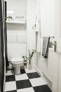 Two Architects Revive Their London Flat With Minimal Furnishings and a Fresh Dose of White - Photo 7 of 7 - Though their wish was to redo the whole bathroom, they decided to stick to a budget and preserve the original black-and-white tiles, which are common in London flats. They ended up keeping it simple and accentuating the color palette with a black-and-white shower curtain and new white storage elements.