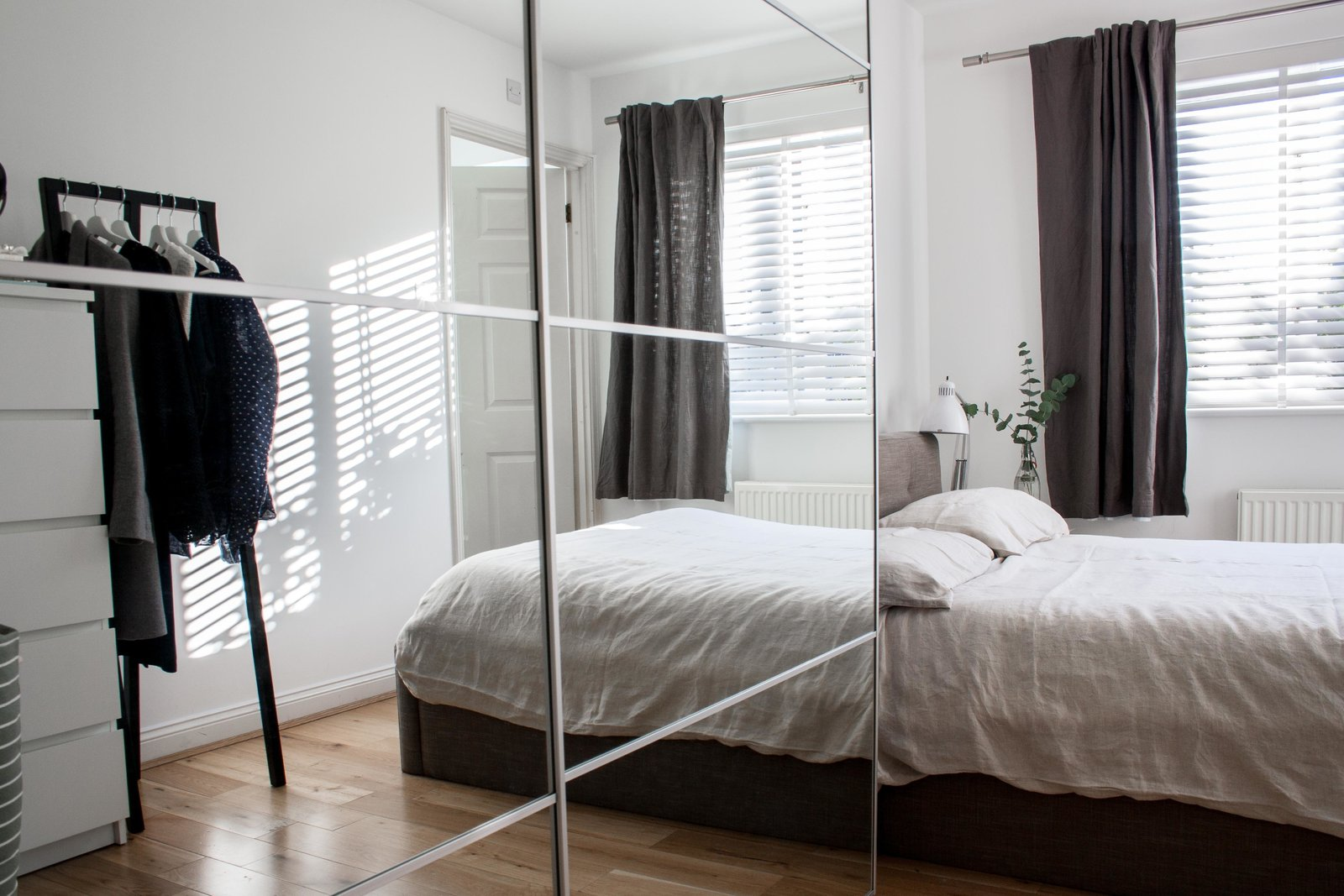 To create more storage and make the small bedroom feel larger, they purchased an Ikea wardrobe with mirrored doors. The clothing rack across from the bed is from HAY. Tagged: Bedroom, Bed, Night Stands, Lamps, Table Lighting, Light Hardwood Floor, and Wardrobe.  Photo 6 of 8 in Two Architects Revive Their London Flat With Minimal Furnishings and a Fresh Dose of White