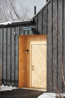 A Modern Mountain Lodge That Will Make You Love Winter Like Never Before - Photo 7 of 13 - The exterior of the structure is wrapped with a board-and-batten facade made of locally-milled wood that's been finished with a dark stain. It's balanced out by sections of natural pine and cedar.