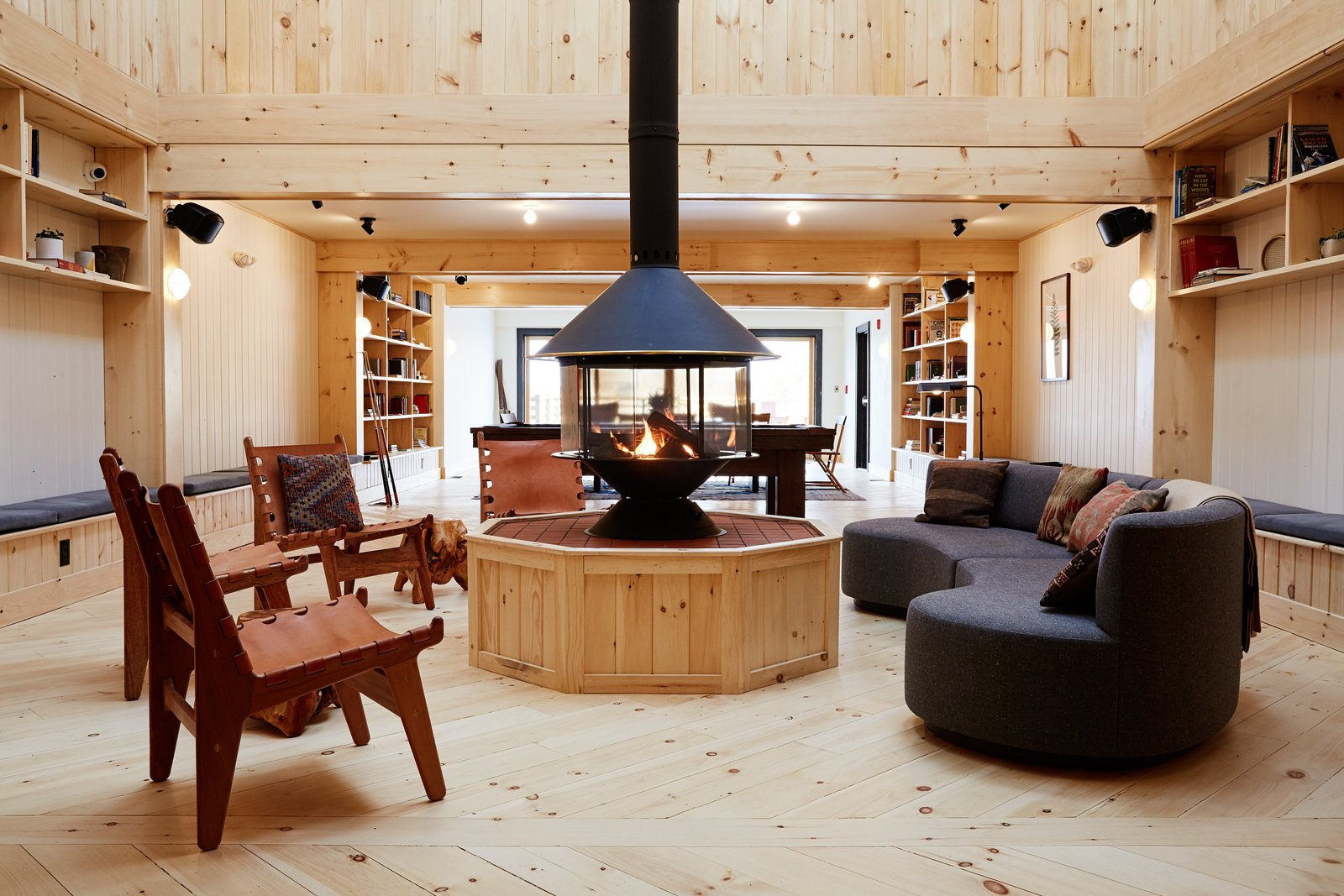 You'll also find a 1,850-square-foot library lounge that can be used as an event space if desired. Tagged: Living Room, Chair, Ceiling Lighting, Gas Burning Fireplace, Wall Lighting, Sofa, and Light Hardwood Floor.  Photo 14 of 14 in A Modern Mountain Lodge That Will Make You Love Winter Like Never Before