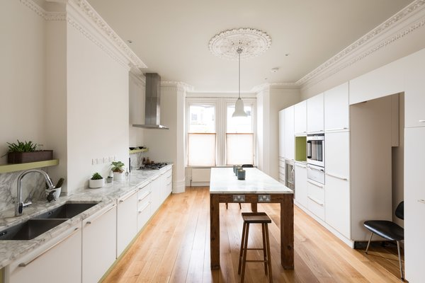 Filled with extensive new cabinetry, marble surfaces, updated appliances, and a large island with embedded power outlets, the kitchen is set up perfectly for entertaining. You can see that the architectural moldings have been preserved, but updated with a fresh coat of paint.