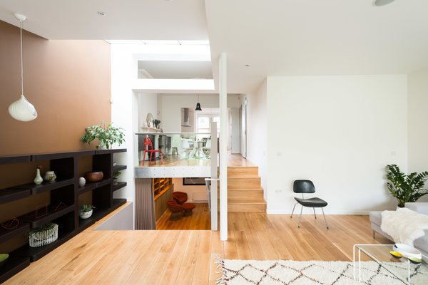 The home's interesting layout becomes clear from this view, which shows the glass balustrade that separates the dining room from the sitting room. The lower steps to the left lead to a media room on the lower ground floor, which then connects to a guest bedroom with an en-suite bathroom.